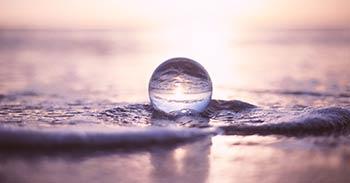 Strand, Wasser und Himmel spiegeln sich in Kugel